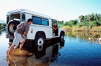 Man pushing a 4x4 across a shallow river