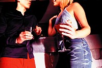 Man and woman holding drinks in nightclub