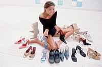 Young woman surrounded by shoes