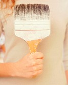 Woman holding a big paint brush