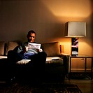 Man holding envelope on sofa
