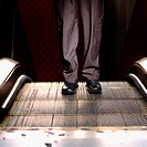 Businessman on escalator (thumbnail)