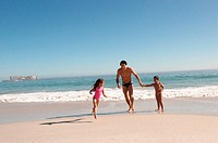 Father and children running on a beach