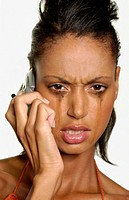 Crying woman using cellular telephone