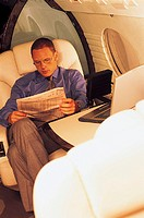 Businessman Reading a Newspaper on a Plane