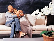 Senior Couple Sitting on a Sofa Cuddling