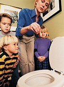 Mother Holding Dead Goldfish over Toilet as Children Watch