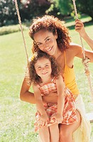 Portrait of a Mother and Her Daughter Sitting on a Swing