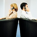 Two Business Colleagues Sitting Back to Back Using their Mobile Phones