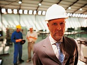 Portrait of a Ceo in a Hard Hat Standing in Front of Two Factory Workers in a Factory
