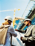 Businessman and Businesswoman Wearing Hard Hats Reading a Blueprint on a Building Site