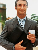Portrait of a Satisfied Businessman Holding a Folder and Wearing An Id Card