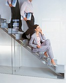 Businesswoman Using a Mobile Phone Sitting on An office Stairway
