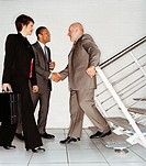 Mature Ceos Shaking Hands at the Bottom of a Stairway in An Office