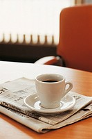 Cup of Coffee With Folded Newspapers on a Desk
