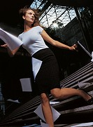 Businesswoman Descending a Staircase Dropping Paperwork