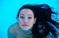 Asian woman in pool with hair flowing