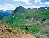 Woman hiking with dog. Yankee Boy Basin. Mount Sneffles Wilderness. Colorado. USA