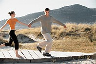 Couple running along a boardwalk (thumbnail)