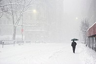 Person walking along snow-covered street (thumbnail)