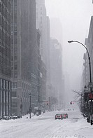 Cars waiting at red traffic light in snow-covered street (thumbnail)