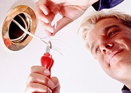 Closeup of electrician adjusting light fitting (thumbnail)