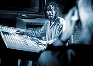 Blue duotone image of man sitting at mixing desk in recording studio (thumbnail)