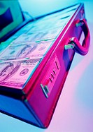 Neon closeup of banknotes in open briefcase (thumbnail)