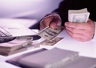 Closeup of buinessman's hands holding and counting banknotes with open filofax and laptop computer (thumbnail)