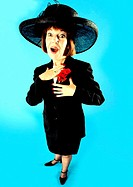 Woman in smart suit and big hat looking surprised and pleased (thumbnail)