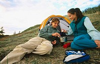Couple cooking meal by tent. Chugach State Park. Southcentral Alaska
