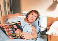Film, ´Elling´, NOR 2001, Regie: Peter Naess Szene mit Per Christian Ellefsen    Männerzeitschrift lesend, im Bett liegend