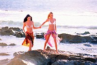 Two females holding hands at the beach