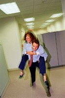 Businessman giving businesswoman piggyback ride