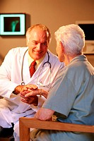 A mature adult female patient talking to a mature adult male doctor wearing a lab coat and stethoscope around his neck