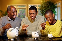 Three generations of men with piggy banks
