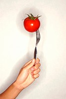 Woman´s hand holding fork with tomato