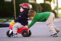 pushing boy on toy tricycle