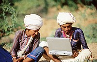 Two Indian rural men in white turbans on laptop.
