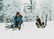 Young Couple Outdoors Riding Sledges