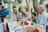 Portrait of Grandparents and Family Outdoors in a Garden Enjoying a Meal