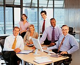 Portrait of a Six Business Executives Around a Desk in their Open Plan Office