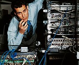 Young Man Using a Mobile Phone By a Stack of Servers