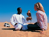 Man With a Falcon and Dressed in Traditional Middle Eastern Clothing Sitting Face to Face With a Woman in the Desert