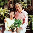 Portrait of a Couple Holding Potted Plants in a Gardening Shop