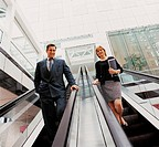 Ceo and a Businesswoman Standing on a Descending Escalator