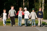 Eight year old school friends, and one four year old younger brother, holding hands. Medevi, Sweden