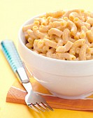 Macaroni and cheese on yellow with blue fork