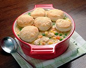 Chicken pot pie with individual biscuit toppings in a red crock