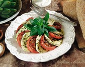 Fresh mozzarella and tomato with basil in a pesto sauce